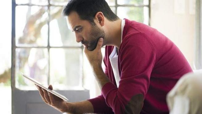 Un hombre utilizando su tablet en su hogar.