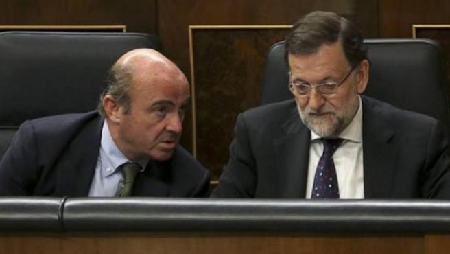 El ministro de Economía, Luis de Guindos, junto al presidente del Gobierno, Mariano Rajoy, en el Congreso.
