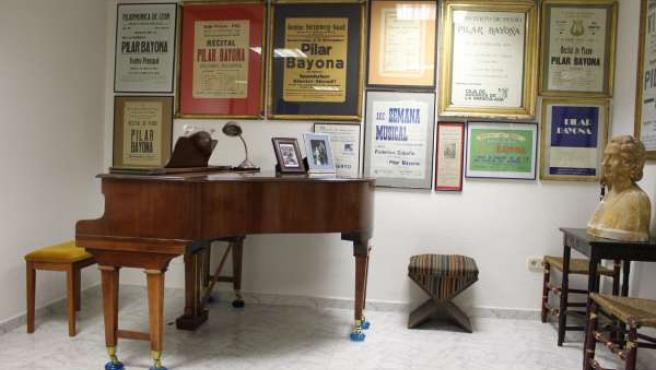 Vista del piano colín Weber con carteles de actuaciones de Pilar Bayona al fondo