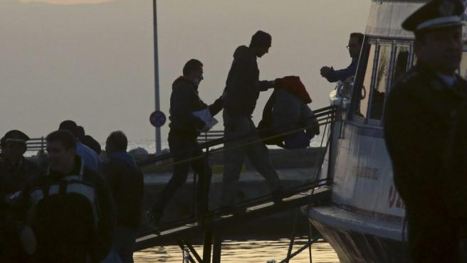 Dos migrantes suben a uno de los barcos que les llevará desde la isla de Lesbos a Turquía. Grecia inició este lunes el proceso de deportaciones de refugiados desde las islas del Egeo oriental al país otomano.