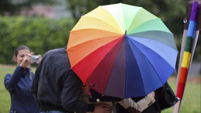 Varias personas posan bajo una paraguas multicolor el Día Internacional contra la Homofobia.