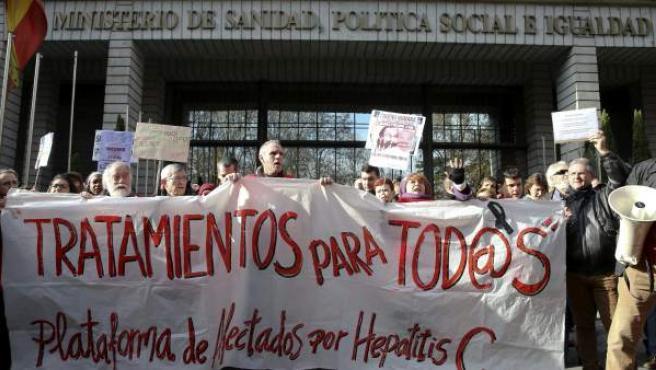 Varias personas participan en una cadena humana, organizada por la Plataforma de Afectados por la Hepatitis C, rodeando el Ministerio de Sanidad.