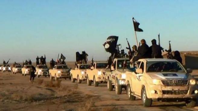 Imagen, sin fecha, difundida por Estado Islámico donde varios militantes sostienen armas y ondean sus banderas en sus vehículos en un convoy que se dirige a la ciudad siria de Raqqa.