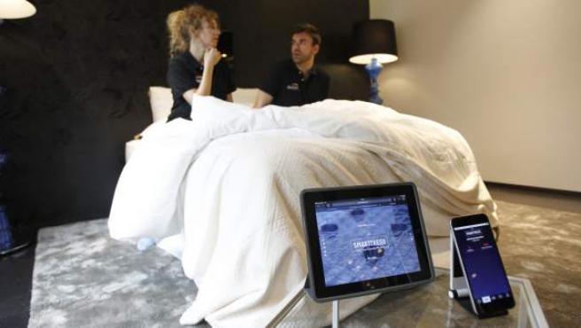 Dos personas muestran el primer colchón inteligente del mundo que detecta una infidelidad.