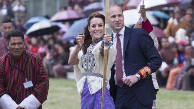 El príncipe Guillermo de Inglaterra (d) y su esposa, la duquesa Catalina de Cambridge (c), durante una demostración de tiro con arco en Thimpu, Bután.