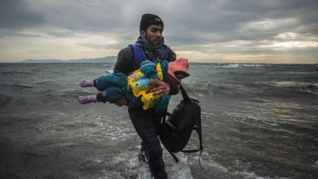 Un refugiado lleva en brazos a un bebé al bajar de una embarcación junto a más refugiados y migrantes en la isla griega de Lesbos.