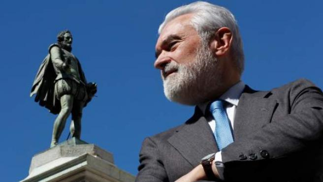 El director de la RAE ante la estatua de Cervantes en la Plaza de las Cortes, frente al Congreso de los Diputados.