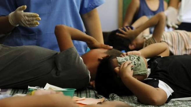 Jóvenes filipinos reaccionan con dolor mientras médicos les practican una circuncisión encima de varios pupitres en un colegio en Markina.