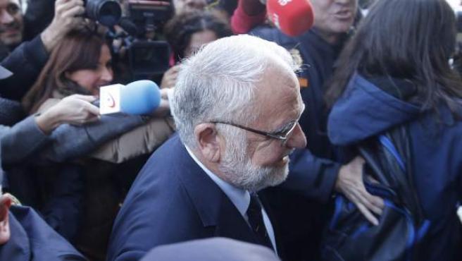 Cotino se dirige a la puerta del Palacio de Justicia de Valencia rodeado de periodistas, policías y manifestantes.