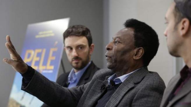 """El exfutbolista brasileño Pelé (c) habla junto al escritor estadounidense Michael Zimbalist (i) y al director Jeff Zimbalist en una rueda de prensa sobre la película """"Pelé, el nacimiento de una leyenda""""."""