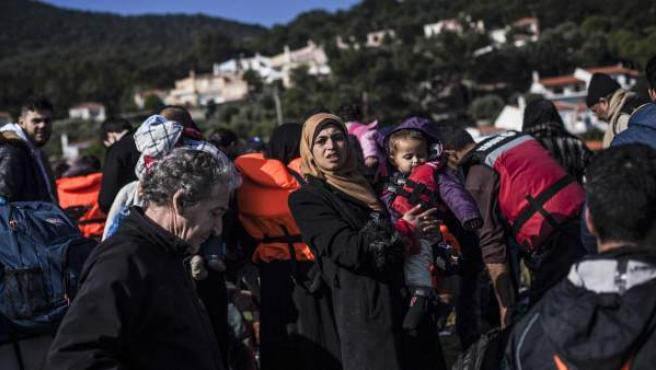 Una refugiada siria sostiene a un bebé en sus brazos a su llegada a la isla griega de Lesbos.