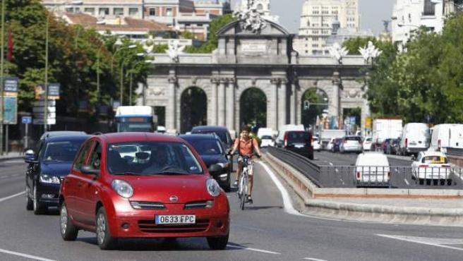 Ciclista rodeado de coches en el giro de la calle de Alcalá hacia la calle de Velázquez.