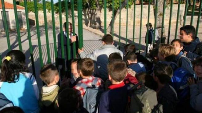 Varios niños en la entrada de un colegio.