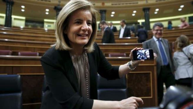Báñez muestra la fotografía que se ha realizado con los periodistas gráficos antes de que comenzara esta mañana en el Congreso el último pleno de la XI Legislatura.
