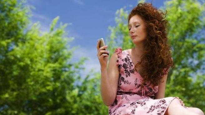 Mujer observando la pantalla de un móvil.
