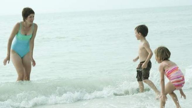 Una mujer disfruta con sus dos hijos en la playa.