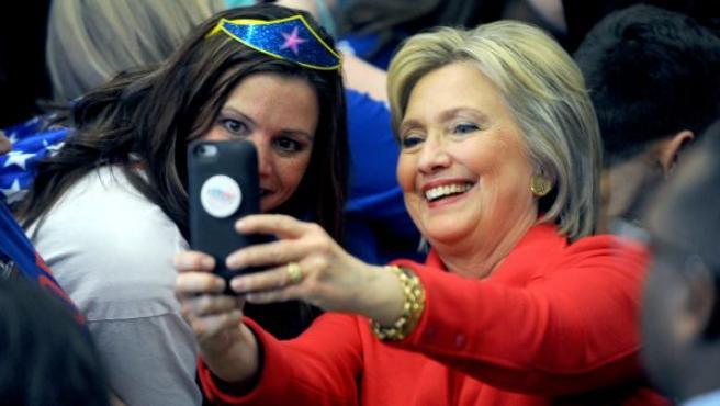 La exprimera dama de EE UU Hillary Clinton se hace una foto con una admiradora en un acto de precampaña demócrata en el Washington HighSchool de Cedar Rapids, Iowa.