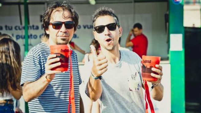 Dos asistentes al Low Festival con vasos reutilizables.