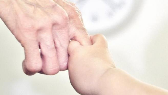 Un abuelo y su nieto se dan la mano.