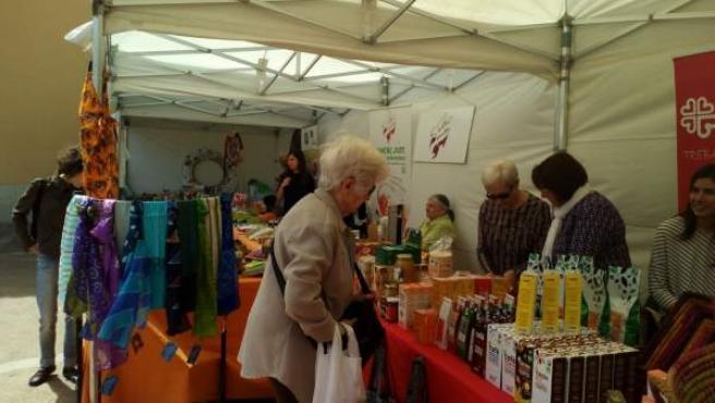 Una mujer visita un puesto de comercio justo de Cáritas.