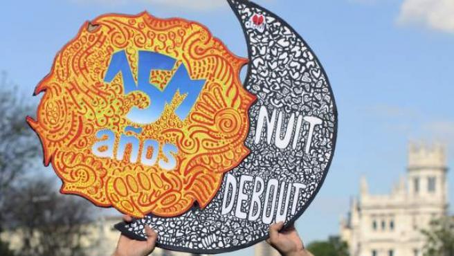 Uno de los participantes en la manifestación entre la Plaza de Cibeles y la Puerta del Sol para conmemorar el quinto aniversario del movimiento 15-M.