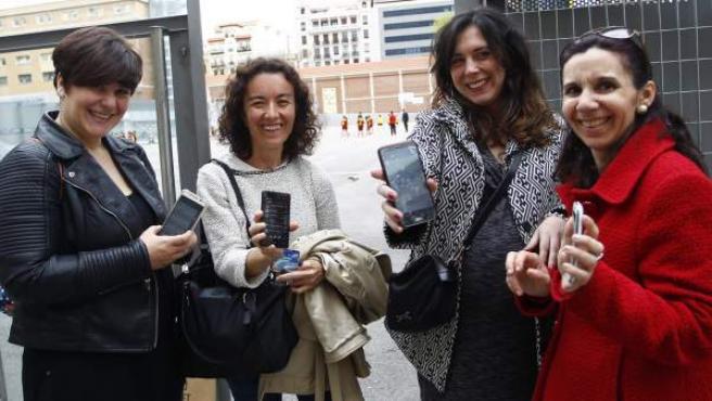 Nuria, Encarna, María y Paloma (de izquierda a derecha) comparten grupo de Whatsapp de madres en una clase de Primaria. En la imagen, en la puerta del colegio de sus hijos en Madrid.