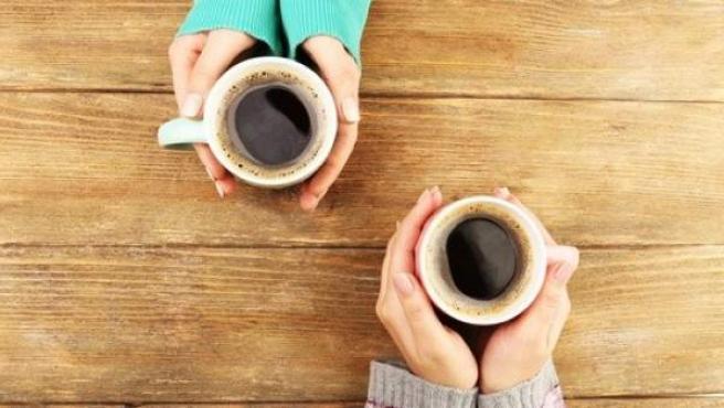 Dos personas con tazas de café.