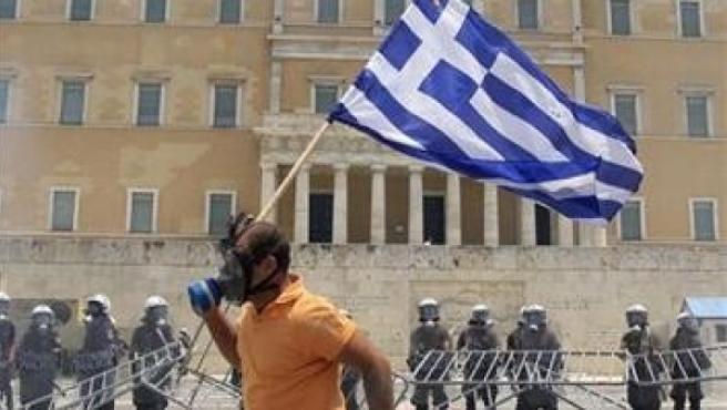 Un manifestante corre ante el Parlamento griego.