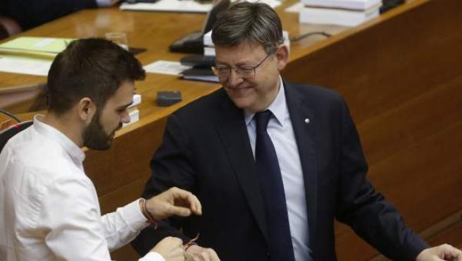 El portavoz de Compromís en Les Corts, Fran Ferri, ha obsqeuiado al presidente de la Generalitat, Ximo Puig, con una pulsera LGTB, que este se ha puesto en su muñeca durante la sesión de control de este jueves.