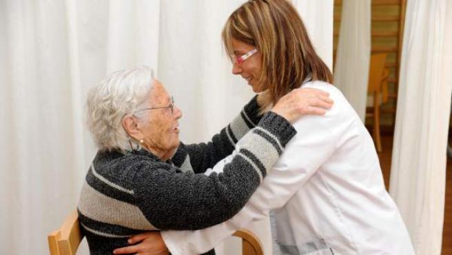 Una anciana dependiente, atendida por una profesional sanitaria.