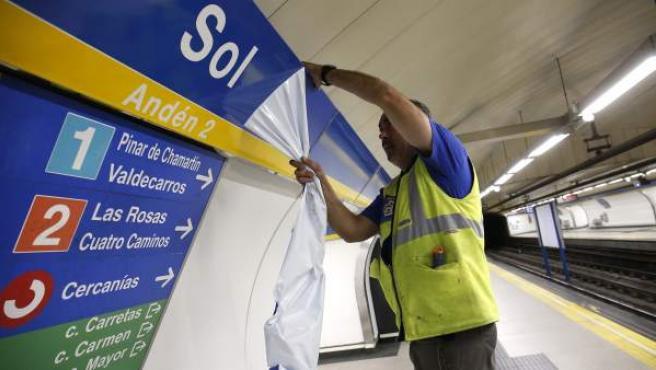 Un trabajador coloca la nueva señalización de la estación de metro de Sol, tras finalizar el patrocinio de Vodafone.
