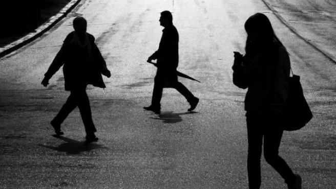 Tres personas cruzan la calle bajo la lluvia Auckland central, Nueva Zelanda.