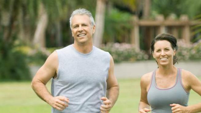 Un hombre y una mujer maduros, corriendo al aire libre.