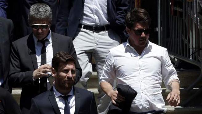 El jugador del FC Barcelona Lionel Messi (c), junto a su padre, Jorge Horacio Messi (detrás), y su hermano Rodrigo Messi, sale de la Audiencia de Barcelona.