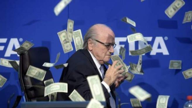 El presidente de la FIFA, Joseph Blatter, bajo una lluvia de billetes que le lanzó el humorista británico Simon Brodkin, durante una rueda de prensa para presentar los resultados de la reunión del Comité Ejecutivo de la FIFA en su sede de Zúrich, Suiza, en julio de 2015.