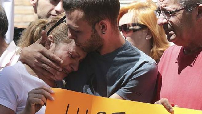 Alejandro Fernández (c), el joven granadino de 24 años condenado por pagar 79 euros con una tarjeta que resultó ser falsa, consuela a su madre durante la concentración celebrada a las puertas de su trabajo en una cafetería del entorno de la plaza de Toros de Granada.