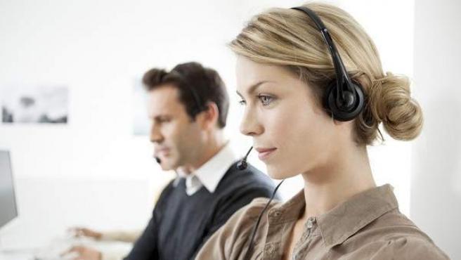 Dos teleoperadores atienden llamadas en un Call-Center.