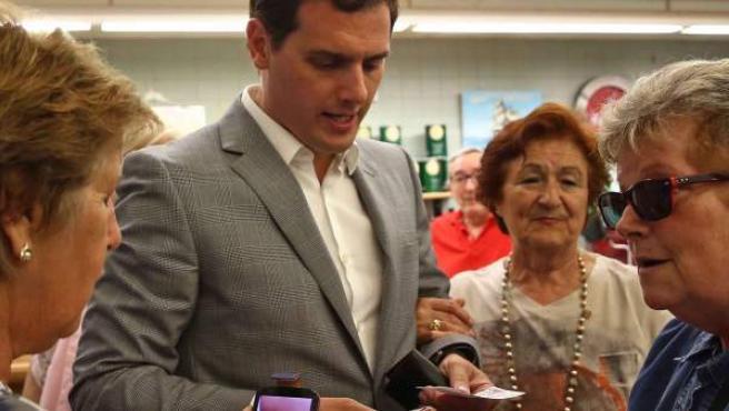 El candidato de Ciudadanos a la Moncloa, Albert Rivera, compra unos cupones de lotería durante su visita al Casal de mayores Can Saladrigas en Barcelona.