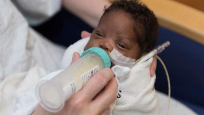 Bebé prematuro tomando un biberón de leche materna.