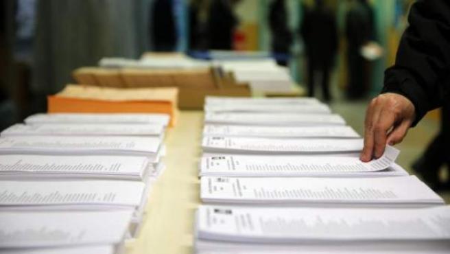 Un ciudadano coge una papeleta en un colegio electoral durante la jornada electoral del pasado 20 de diciembre.