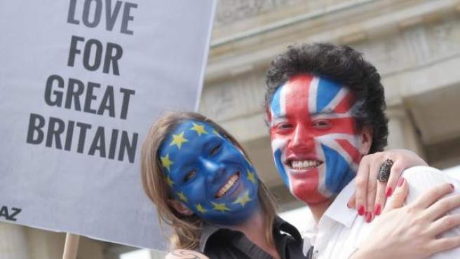 Una pareja con la cara pintada de las banderas del Reino Unido y la UE sostiene una pancarta en apoyo a la permanencia del país en la Unión Europea.