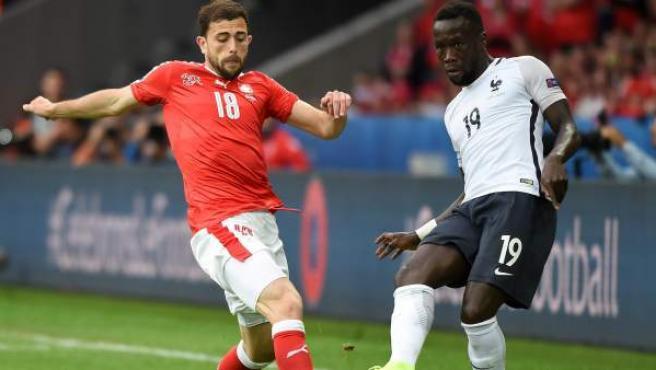 Mehmedi, de Suiza, y Sagna, de Francia, en el partido que enfrentó a sus selecciones.