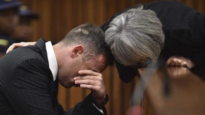 El atleta sudafricano Oscar Pistorius recibe palabras de aliento de una mujer no identificada, mientras permanece sentado en el banquillo de los acusados durante una vista para dictar la pena que debe cumplir por el asesinato de su novia, la modelo Reeva Steenkam, en el Tribunal Superior del Norte de Gautengal, en Pretoria (Sudáfrica).