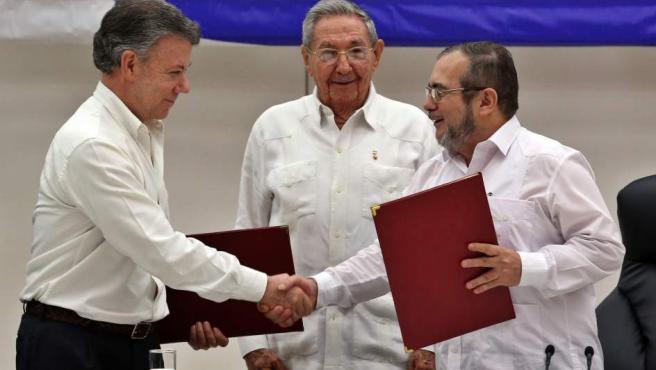 """El delegado de las FARC en Cuba, Rodrigo Londoño Echeverri, alias """"Timochenko"""" (d) y el presidente de Colombia, Juan Manuel Santos (i) junto a el presidente de Cuba, Raúl Castro (c) sostienen en sus manos el acuerdo de paz entre el Gobierno colombiano y las FARC."""