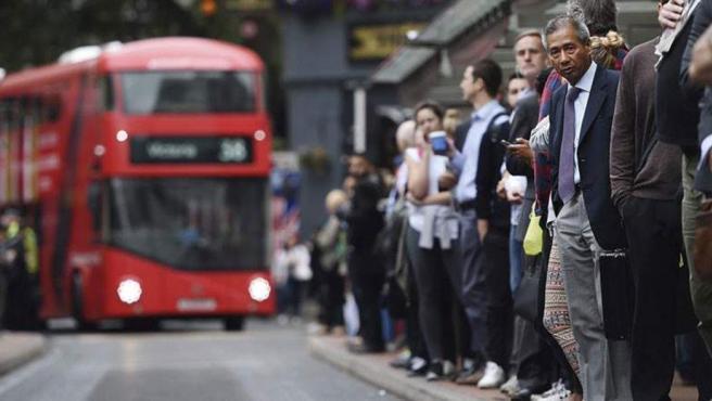 Trabajadores esperan en una parada de autobús de Londres.