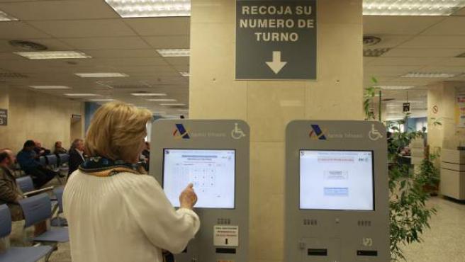 Una mujer saca número en una oficina de la Agencia Tributaria durante la campaña de la Renta.