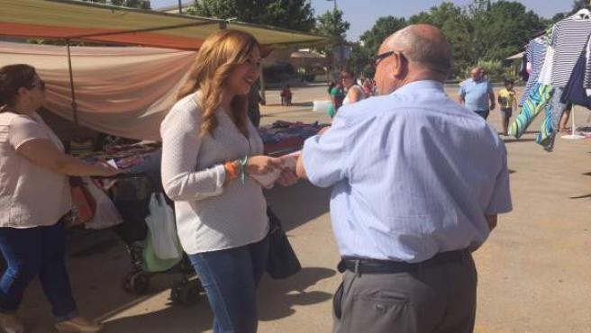 La candidata de C's Raquel Morales convsersa con un hombre en el mercadillo.