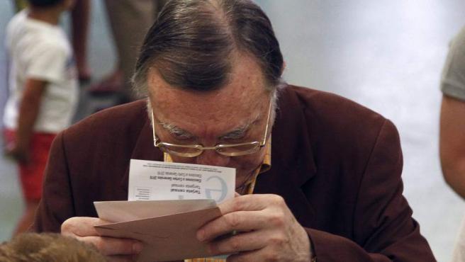 Un ciudadano verifica el número de mesa al que dirigirse en el colegio electoral Infant Jesús de Barcelona durante la jornada de elecciones generales.