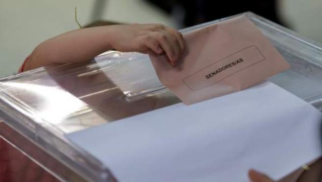 Una niña intenta meter por sí misma el sobre en la urna con el voto de su madre para el Senado, este mediodía en un colegio electoral del barrio de Triana en Sevilla.