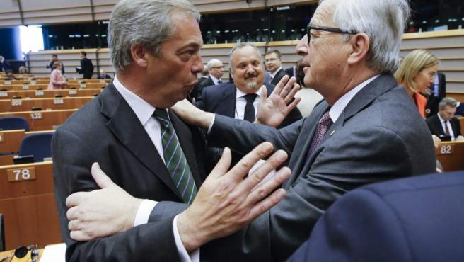 El presidente de la Comisión Europea, Jean-Claude Juncker (d), saluda al líder del Partido de la Independencia de Reino Unido (UKIP), Nigel Farage (i), al inicio de una sesión plenaria extraordinaria del Parlamento Europeo.
